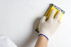После шпаклевки стены ее необходимо отшлифовать при помощи шкурки.